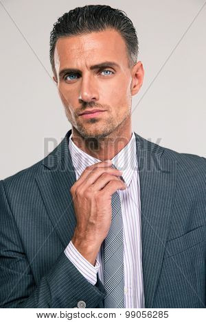 Closeup portrait of a businessman straightening his tie isolated on a white background