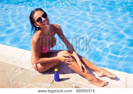 Portrait of a smiling cute woman sitting near swim pool and applying sun cream outdoors