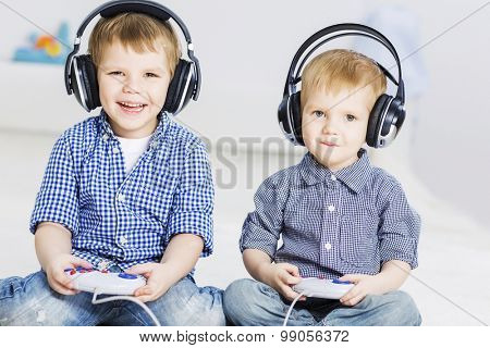 Cute boys playing game in wireless headphones