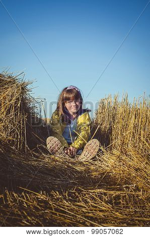 Little girl sitting in the field, including the tapered ears