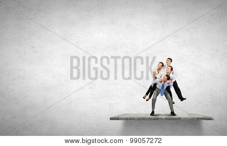 Businesspeople riding on back of their colleague