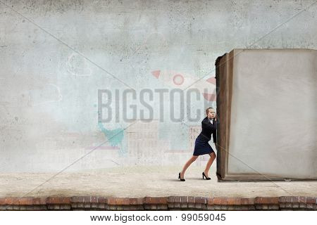 Young woman making effort to push huge old book