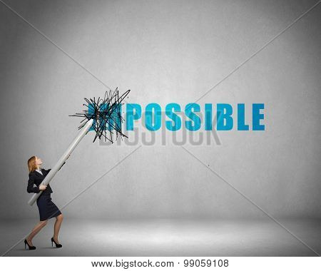 Young businesswoman with huge pencil changing word impossible