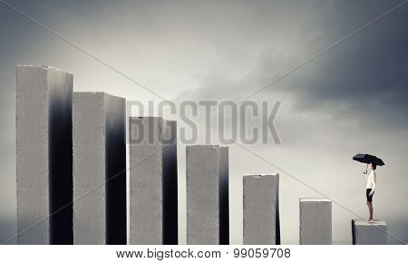 Young businesswoman with black umbrella standing on falling graph