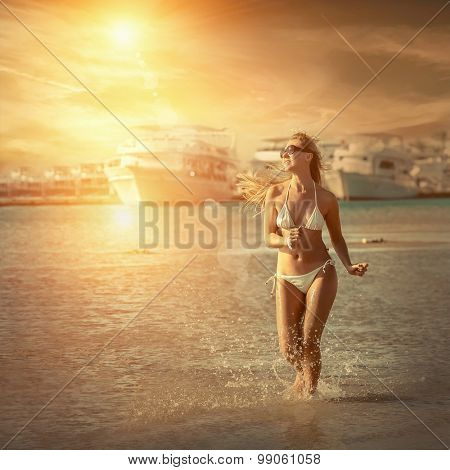 Happiness female running on the beach, yachts background and under sunlight