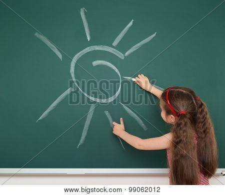 girl drawing sun by white chalk on school board