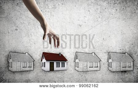 Human hand grabs drawn on paper house