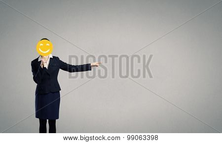 Unrecognizable businesswoman hiding her face behind mask and showing direction