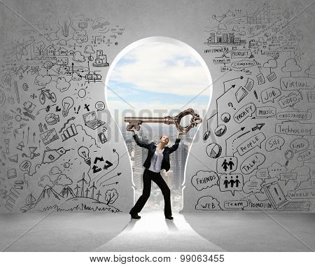 Young businesswoman and keyhole at background lifting big key above head