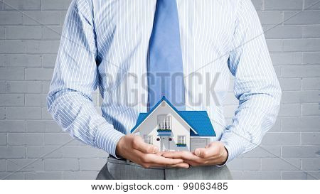 Close up of businessman holding house model in hands