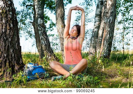 Young woman hiker stretching in a forest