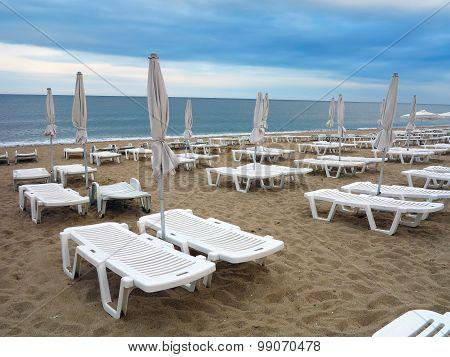 Beach Chairs And Umbrella On The Sand Near Sea, Blue Sky