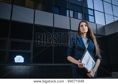 Successful Beautiful Young Business Woman Standing Against A Background Of Buildings And Holding Fol