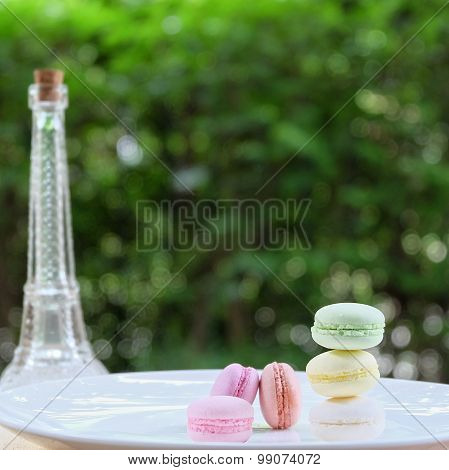 Lovely Pastel Colors Macarons On White Plate And Mini Eiffle Tower With Green Blur Background