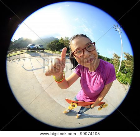 young woman skateboarder hold skateboard at skatepark