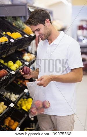 Smiling hansome buying a fruits at supermarket