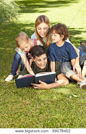Father reading book to family and his two children in a garden