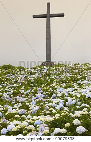 Catholic Cross And Hydrangeas Garden On A Cloudy Day