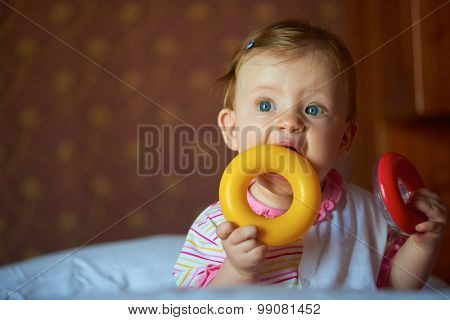 happy baby with first teeth smilling and play with toys