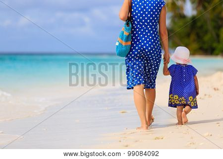 mother and little daughter walking on tropical beach