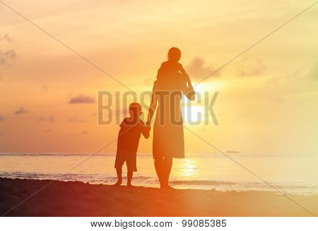 mother with two kids walking on sunset beach