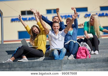 Group portrait  of happy  students outside in front of school sitting on steps have fun