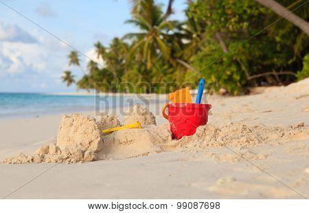 Sand castle on tropical beach and toys