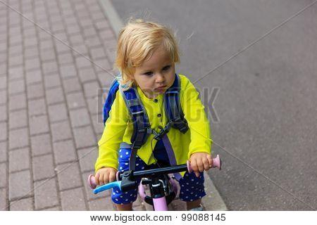 little girl riding runbike outdoors