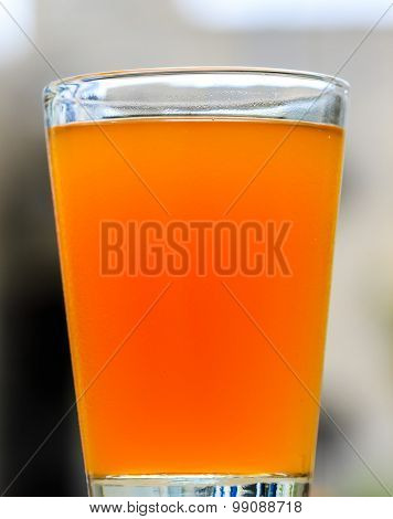 Fresh fruit juice kept in a glass cup on a blurred background