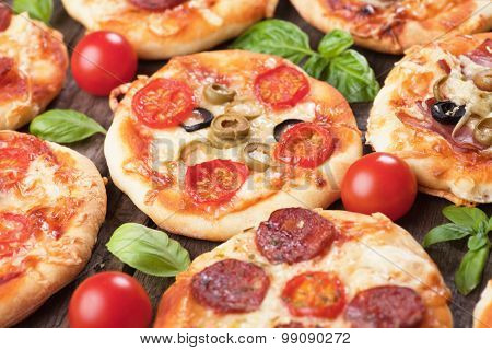 Mini margarita pizzas with cherry tomato, cheese and olives