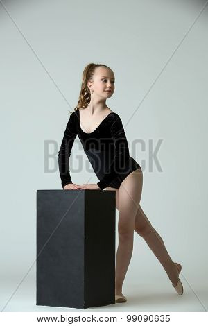 Graceful little gymnast posing with cube