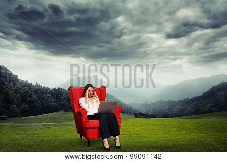 tired businesswoman sitting on red chair over beautiful dark landscape with meadow and lowering sky