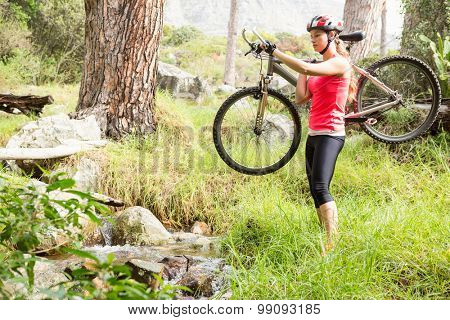 Blonde athlete carrying her mountain bike in the nature