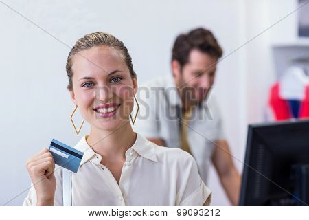 Portrait of smiling woman showing credit card to camera in clothing store