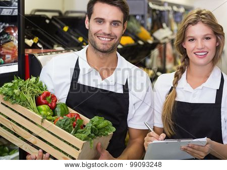 Portrait of two colleagues holding a box with fresh vegetables and writing on notepad at supermarket