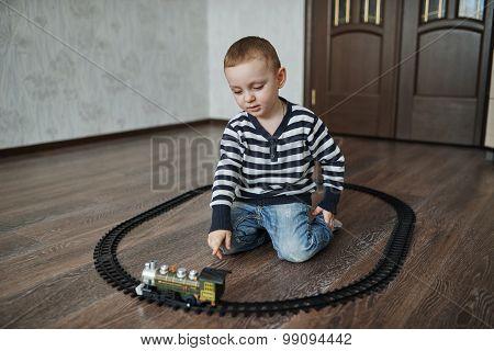 little boy builds toy railroad