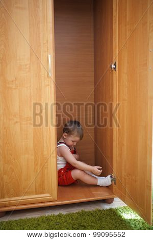 little boy hiding in closet