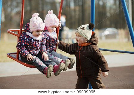 boy rolls girls on swings