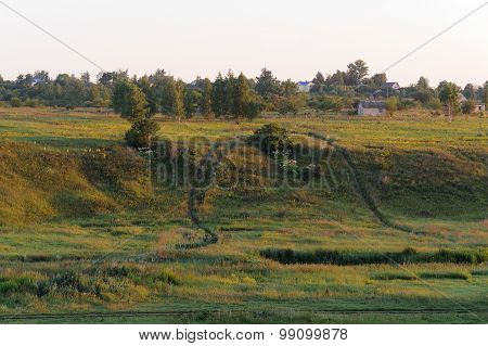 Green Hills With Winding Roads In Summer Sunrise