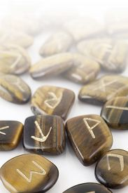 stock photo of rune  - Close up of Rune Stones scattered on a white surface fading into white  - JPG