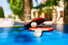 stock photo of ping pong  - Table tennis rackets and ping pong ball on the vacation place background at the summer time - JPG