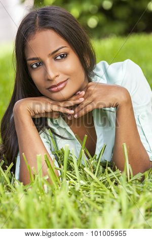 Outdoor portrait of a beautiful Indian Asian young woman or girl outside in summer sunshine laying down resting on her hands