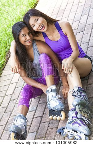 Two young Asian women girls, Chinese and Indian, laughing having fun in line roller skating