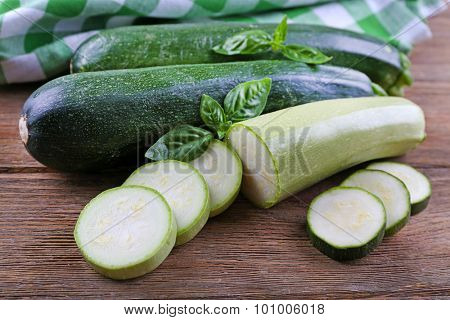 Fresh zucchini with squash and basil on wooden table close up