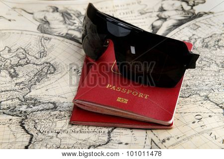 travel concept, two passports and sunglasses on the old map