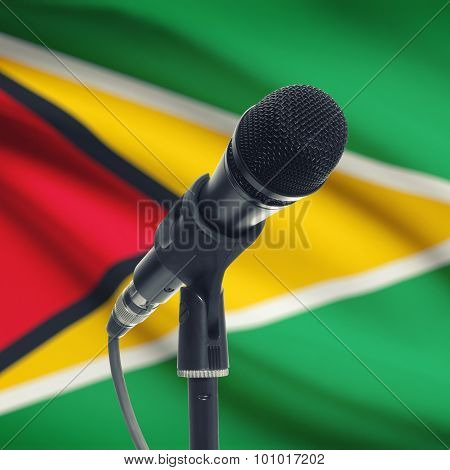Microphone On Stand With National Flag On Background - Guyana