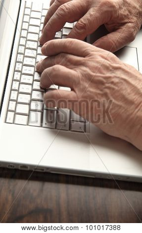 Older man works on laptop