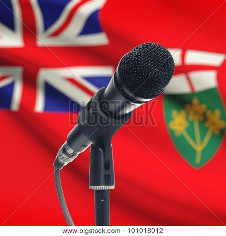 Microphone On Stand With Canadian Province Flag On Background - Ontario