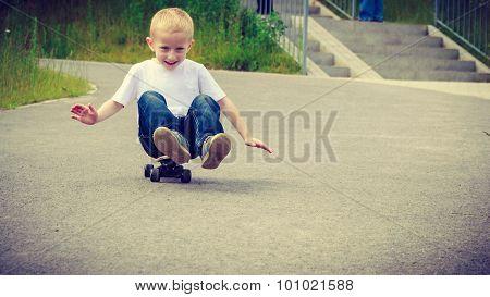 Child Kid Sitting On Skateboard Having Fun Outdoor
