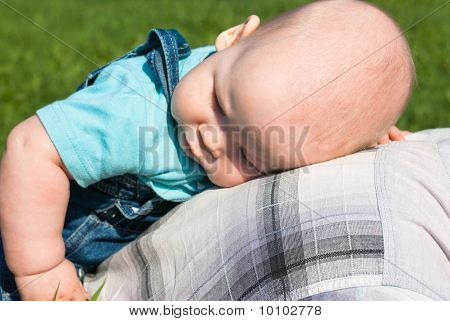 A Little Boy Lying On His Back With Their Father
